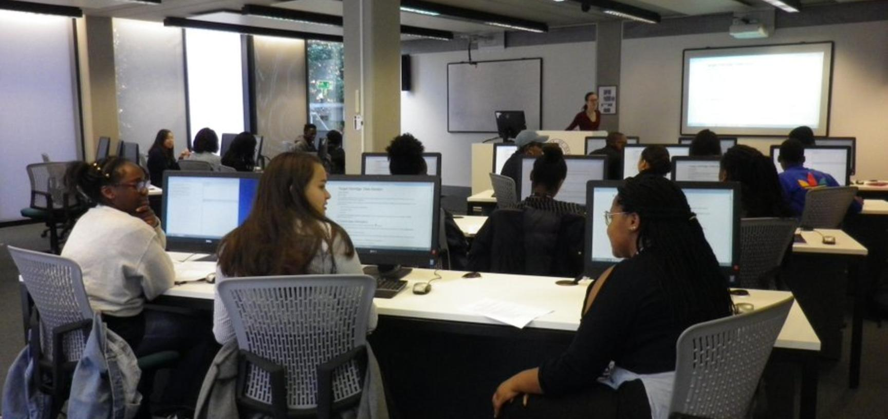 View from the back of computer lab with students in front of desktops and lecturer at the front next to projector screen