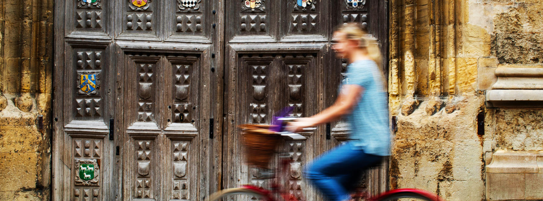 Blurred person cycling in front Oxford University college wooden gate
