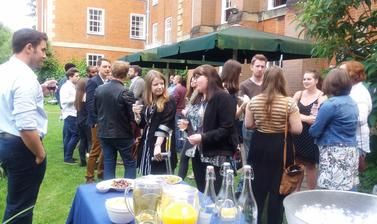 Summer Institute participants and lecturer at welcome reception in garden outside red building