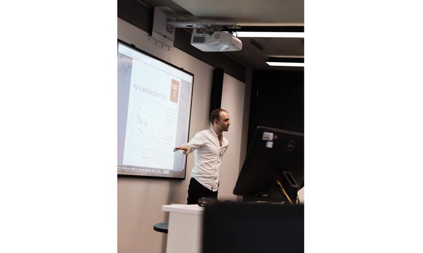 Lecturer standing in front of projector explaining plot